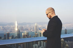 Male skilled CEO is using cell telephone during work break. Confident businessman is typing text message on mobile phone, while is standing on roof building Stock Image