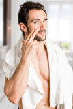 Male Skin Care. Male applying moisturizer to her face in the bathroom Royalty Free Stock Photography