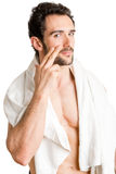 Male Skin Care. Male applying moisturizer to her face, isolated in white Royalty Free Stock Photography