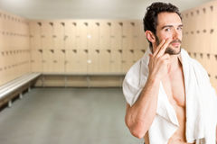 Male Skin Care. Male applying moisturizer to her face in a locker room Stock Photo