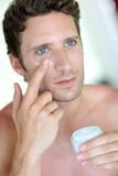 Male skincare. Handsome man applying moisturizing cream Stock Images