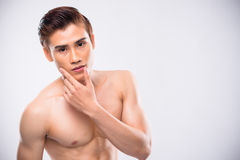 Male skincare. Portrait of handsome Asian man touching soft skin of his face Royalty Free Stock Images