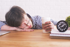 Male sleeping in office. Young male with coffee in hand sleeping on wooden office desk with clock and notepads on white brick background Royalty Free Stock Images