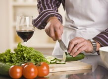 Male Slicing Cucumber for a Salad. Male hands slicing cucumber on a cutting board. torso and hand shot. square Stock Photography