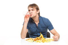 Male slut drinking soda and eating chips. desk. Cesspool Royalty Free Stock Photos