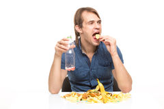 Male slut drinking soda and eating chips. desk Royalty Free Stock Image