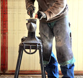 Male smithy working. Male smithy working on a horseshoe inside a stable Stock Photo