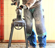 Male smithy working. Male smithy working on a horseshoe inside a stable Royalty Free Stock Photography
