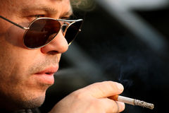 Male smoker wearing sunglasses. Smoking a cigarette outdoors Royalty Free Stock Photography