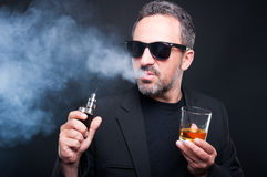 Male smoking an electronic cigarette. And drinking fine alcohol on black background Stock Photos