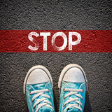 Male sneakers and word stop. Male sneakers on the asphalt road with drawn word stop Royalty Free Stock Photo