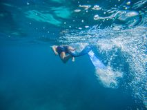 Young man swimming and snorkeling with mask and fins in clear blue water stock photos
