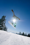 Male Snowboarder Catches Big Air. Male Snowboarder Catches Big Air on a Bright Sunny Day Royalty Free Stock Photography
