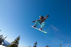 Male Snowboarder Catches Big Air. Male Snowboarder Catches Big Air on a Bright Sunny Day Stock Image