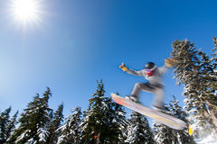 Male Snowboarder Catches Big Air. Male Snowboarder Catches Big Air on a Bright Sunny Day Royalty Free Stock Image