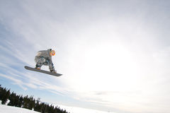 Male Snowboarder Catches Big Air. Male Snowboarder Catches Big Air on a Bright Sunny Day Stock Photography