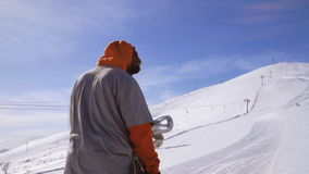 Male snowboarder climbs uphill on foot stock video