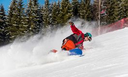 Snowboarder riding in the mountains on a sunny winter day Stock Images