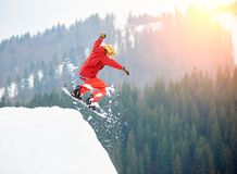 Male snowboarder freerider jumping from the top of the snowy hill with snowboard Stock Photos