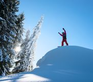 Snowboarder resting on top of the mountain Stock Photos