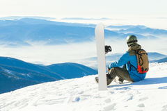 Male snowboarder in helmet sitting at the very top of a mountain and taking a look at landscape Royalty Free Stock Photos