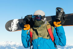 Male snowboarder holding board behind his sholders at the very top of a mountain. Male snowboarder holding board behind his sholders at the top of a mountain Royalty Free Stock Photo