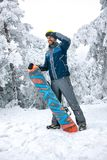 Male snowboarder looking at distance on ski terrain. Male snowboarder holding snowboard and looking at distance on ski terrain Stock Image