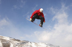 Male Snowboarder Jumping Against Cloudy Sky Royalty Free Stock Image