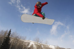 Male Snowboarder Jumping Against Sky. Low angle view of young male snowboarder jumping against sky Royalty Free Stock Photography
