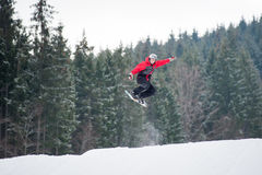 Male snowboarder jumping over the slope in winter day. Male boarder on the snowboard jumping over the slope in winter with snowy slope and snow-covered firs in Royalty Free Stock Photos