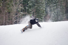 Male snowboarder jumping over the slope in winter day. Snowboarder rides over fresh snow on the slope in winter, extreme sport Stock Photo