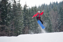Male snowboarder jumping over the slope in winter day. Young male on the snowboard jumping over the slope in winter with snowy slope and snow-covered firs in Stock Photo