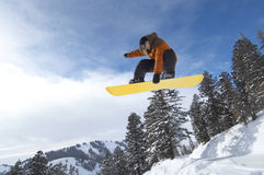 Male Snowboarder Jumping Over Snow Covered Hill. Low angle view of a male snowboarder jumping over snow covered hill against the sky Stock Image
