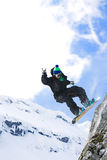 Male snowboarder jumping with snowboard. Caught in mid air Stock Images