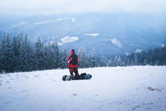 Male snowboarder in mountains. Male snowboarder looks into the distance on snowy mountain slopes Stock Images