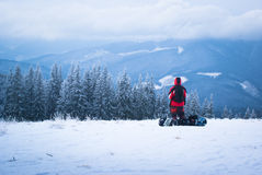 Male snowboarder in mountains. Male snowboarder looks into the distance on snowy mountain slopes Royalty Free Stock Photo