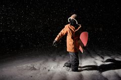 Male snowboarder in orange sport jacket walking on snow with a b. Oard in hand at night royalty free stock photography