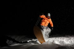 Male snowboarder in orange sportswear balancing on the snowboard at night. Professional male snowboarder dressed in orange sportswear and protective glasses stock images