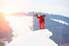 Male snowboarder in a red suit standing on the top of the snowy hill with snowboard in hand. Smiling to the camera at winter ski resort. Skiing and Royalty Free Stock Photo
