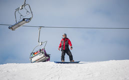 Male snowboarder riding down from the mountain in winter day. Man standing on his snowboard on a ski slope. Snowboarder prepares to make a descent. Ski lifts Royalty Free Stock Photography