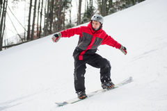 Male snowboarder riding down from the mountain in winter day. Male snowboarder slides down from the mountain in winter day, overlooking the snowy slope at a Stock Images