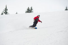 Male snowboarder riding down from the mountain in winter day. Young male snowboarder riding over the slope at the mountains overlooking a ski run on the snowy Royalty Free Stock Photography