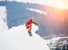Male snowboarder riding from the top of the snowy hill with snowboard at winter ski resort. Skiing and snowboarding concept Stock Photos