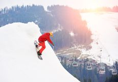 Male snowboarder riding from the top of the snowy slope with snowboard at winter ski resort. Ski slope, ski-lift, forests and mountains on the background Royalty Free Stock Photos