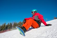 Snowboarder resting on top of the mountain. Male snowboarder sitting, relaxing on the slope of the hill at winter ski resort. Blue sky, forest on the background Stock Photos