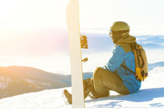 Male snowboarder sitting at the very top of a mountain and looking at the sun-set. Snowboarder sitting at the very top of a mountain and taking a look at Royalty Free Stock Photo