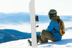 Male snowboarder sitting at the very top of a mountain and taking a look at landscape Stock Photos