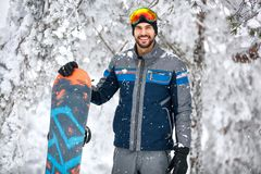 Male snowboarder with ski equipment. At winter vacation Royalty Free Stock Image
