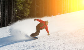 Male snowboarder slides down from the mountain in winter day. Overlooking the snowy slope and at a winter resort. Bukovel Royalty Free Stock Images