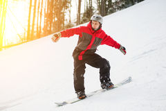 Male snowboarder slides down from the mountain in winter day. Overlooking the snowy slope at a winter resort. Close-up Stock Images